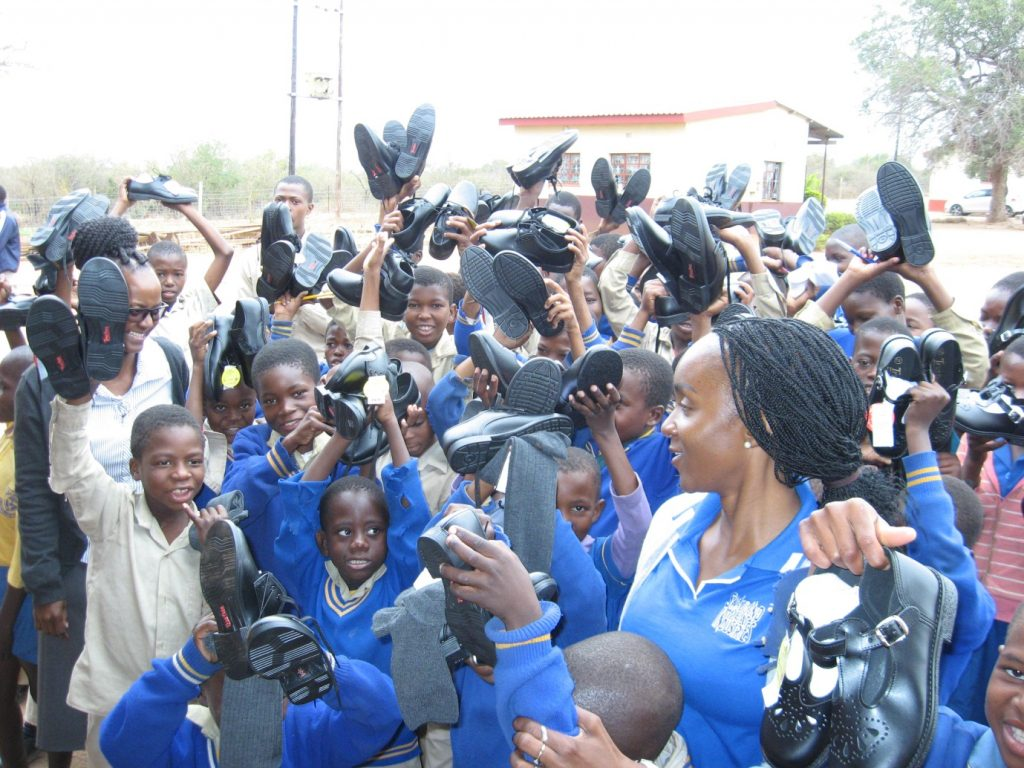 Ms Mhlang surrounded by excited school children holding their new shoes